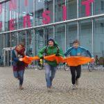 Mit Energie nach vorn sprinten vor dem Glaskasten der Universität